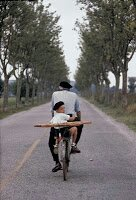 man on bike with child and bread