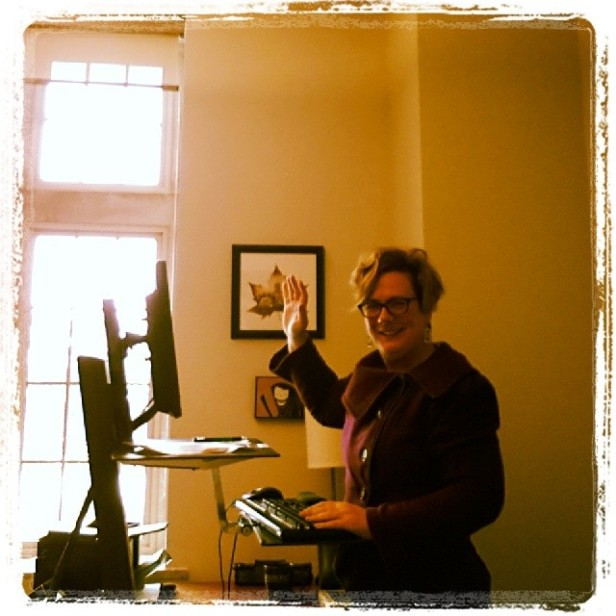 Image: Me waving from my standing desk, learning to use the timer on my phone camera