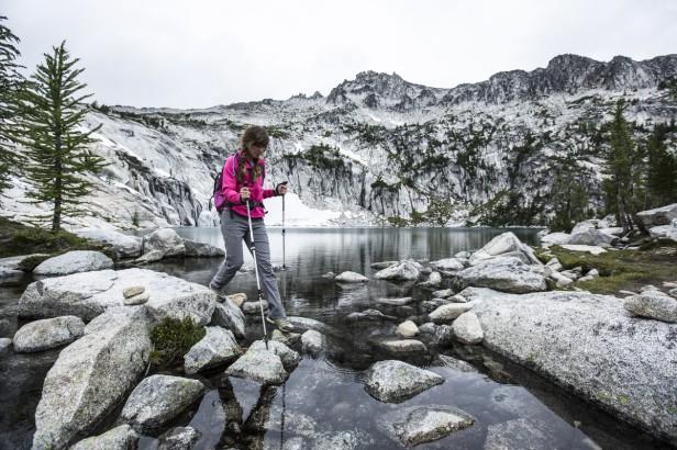 woman hiking across snowy rocks with poles