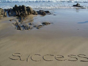 "Beach with the word ""success"" written in the sand."