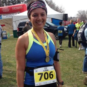 Tracy after crossing the finish line at the 10K Run for Retina.  Big smile, medal, happy runner.
