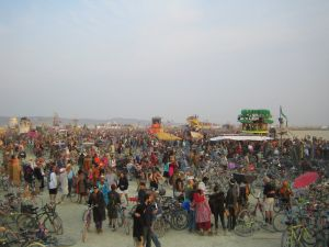 "People and bikes crowding onto the playa for the early morning burning of a stunning art piece called ""Embrace."""