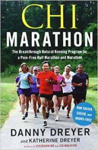 Book cover for chi marathon. A group of eight or nine people running on a wide path with green grass on either side.