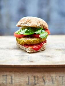 Photo of a vegan chickpea burger from Jamie Oliver, with lettuce, an artisan bun, and tomato.