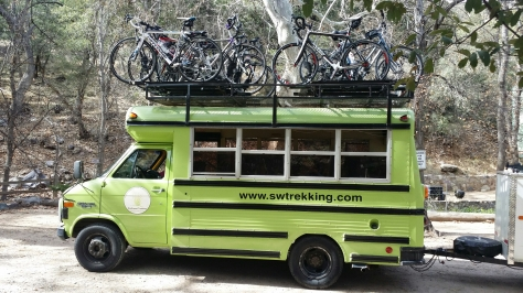 neon green bus with bikes on roof