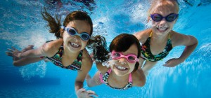 three children under water swimming, smiling.