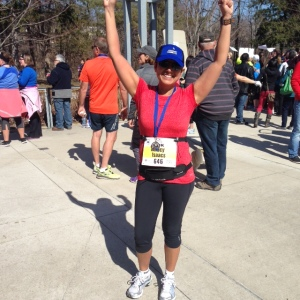 Tracy in a victory pose with hands high in the air, red t-shirt, post run for retina