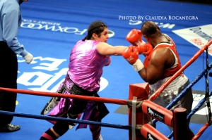 "Sonya ""The Scholar"" Lamonakis, punching in a boxing match. Opponent up against the ropes."