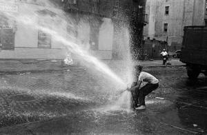 a man opens a fire hydrant in the street in NYC during the heatwave of 1953, water sprays out into the street.
