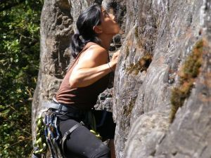 Audrey rock climbing with some visible forearm definition.