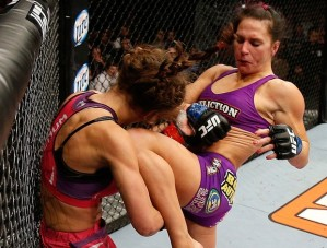 Cat Zingano in a sports bra and little shorts knees a similarly clad Miesha Tate in the face.