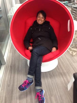 Tracy sitting in a round red chair, looking happy and content.