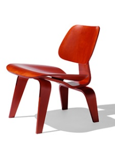 Tracy's favourite chair -- the eames molded plywood chair by Herman Miller, in red. A stylish sleek and low to the ground chair.