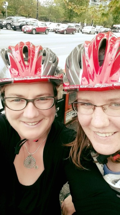 Sam and her daughter Mallory, selfie, big smiles, wearing matching red rental helmets