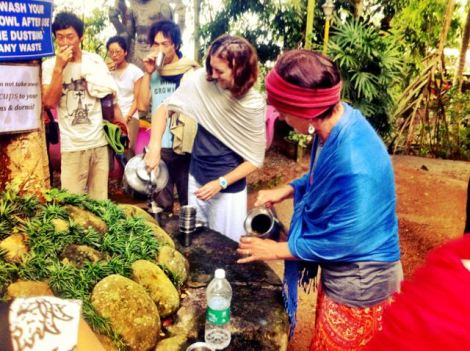 Yogis pouring morning tea in the open air at the ashram