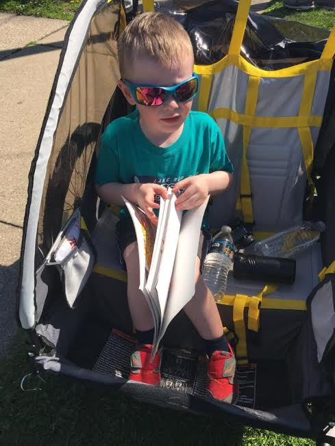 A child wearing sunglasses in a stroller with snacks, a water bottle, and a book.