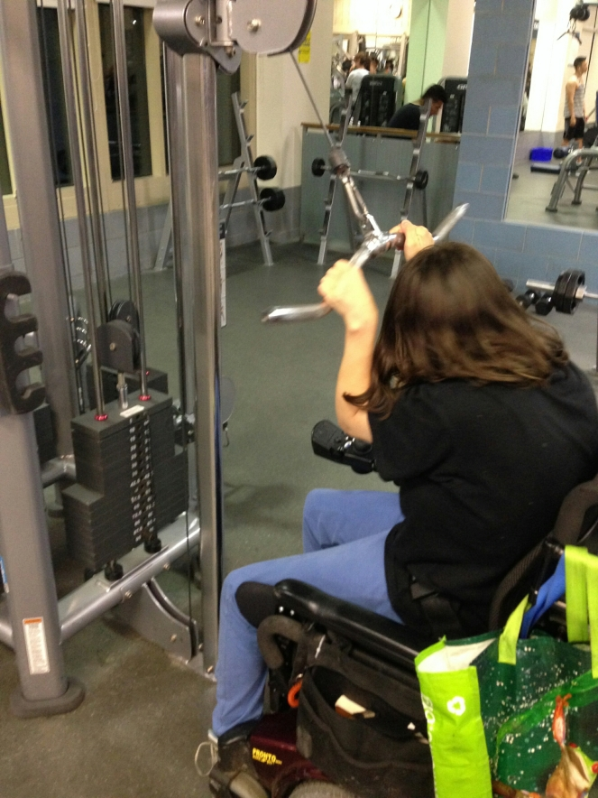 person with shoulder length brown hair, black tshirt and blue pants, using the pull down weight machine in a power chair
