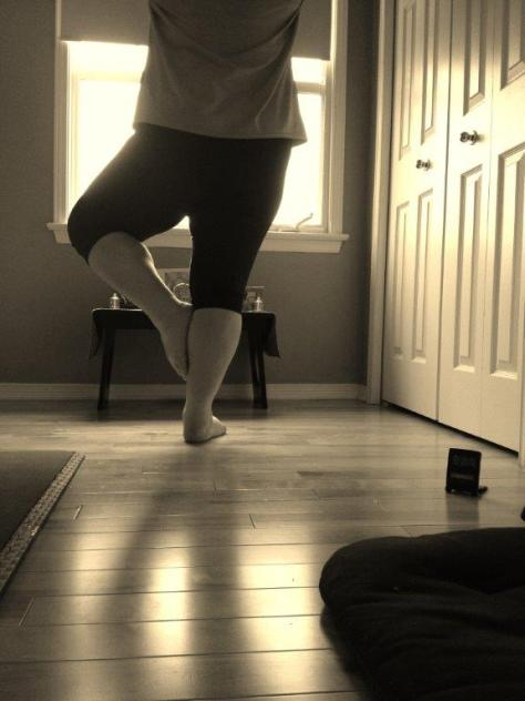 black and white photo of woman doing yoga, tree pose. She's on hardwood floor, in a beam of light and the photo is shot from behind. It's mostly floor, feet, and legs.