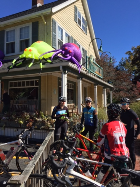 Women cyclists standing outside a New England country store, with bikes in the foreground and two halloween day glo spiders (yellow and purple) on the roof of the store.