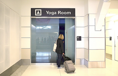 Woman with carryon suitcase entering the yoga room at San Francisco airport.