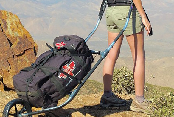 A woman hiking in mountainous desert, towing a large backpack on wheels with a frame,