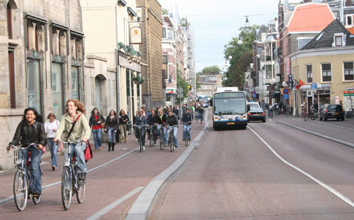 Traffic in a Dutch town, with cyclists in their lanes and cards and busses in their lanes.