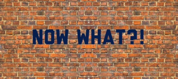 "A brick wall with the words ""Now What?!"""