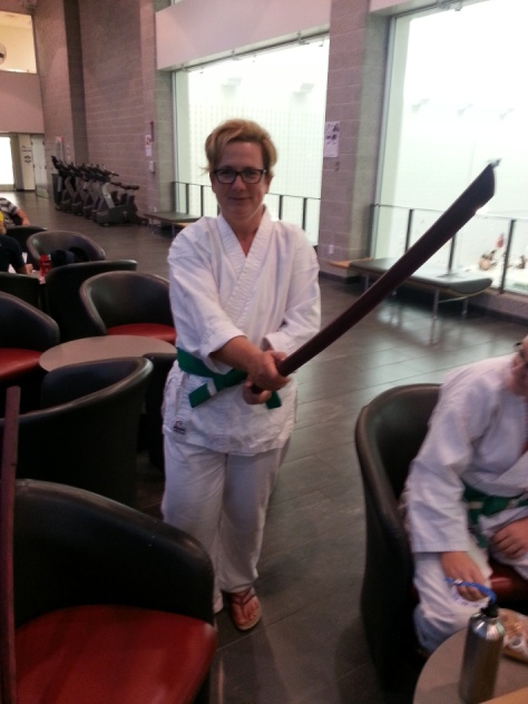 Sam with wooden sword, while wearing Aikido gi, in the lobby of the student rec centre
