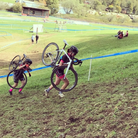 The author carrying her bike up a hill at a cx race