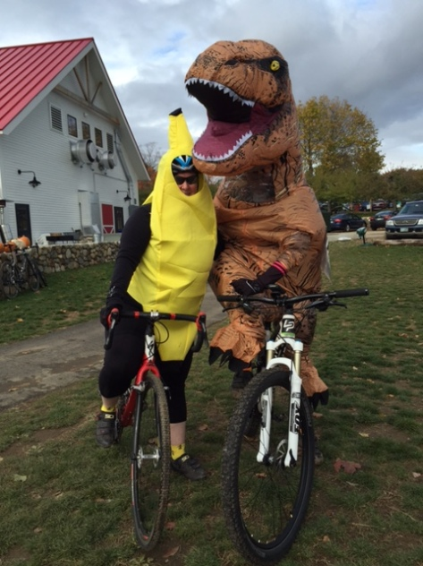 Banana and T. rex in costume on bikes