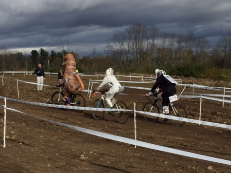 group of riders on cross course, led by T. rex