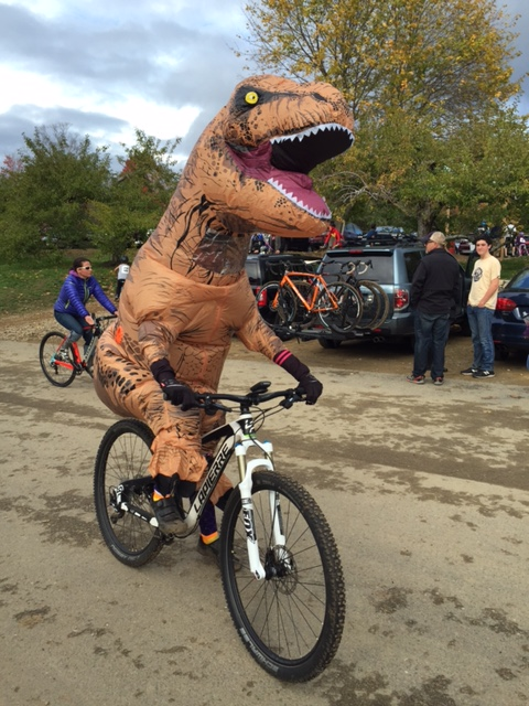 T rex. costumed rider on mountain bike