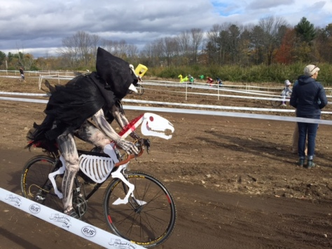 Racer in skelton costume with black hood and skeleton cardboard outline on bike, riding course