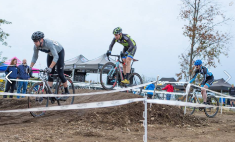 Male cross racers riding over a pump track muddy bump.