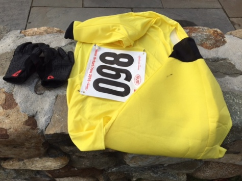 My banana costume with its race number, and black cycling gloves on a wall.