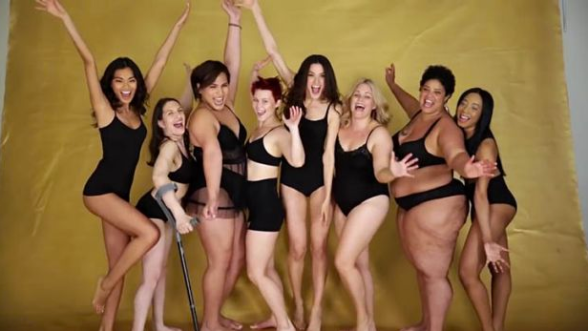A photo of a group of different sizes and colors and abilities of women in black underwear, smiling and celebrating their bodies