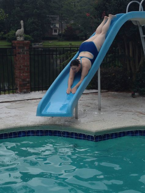 The author, slide down a sliding board into a pool,. head first, wearing a blue bathing suit