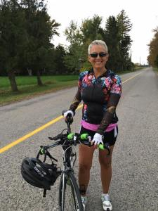 Tracy on a country road holding her new time trial bike with the helmet slung over the handle bars in fall 2015. Caption reads