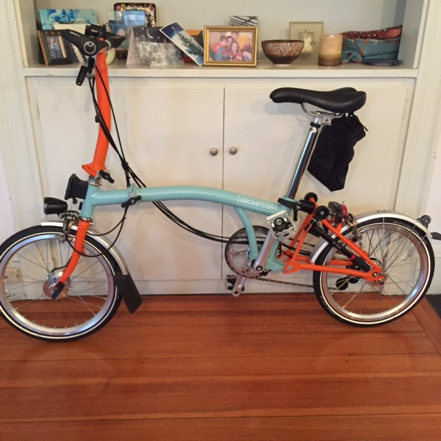 A brompton folding bike, in sea green and orange.