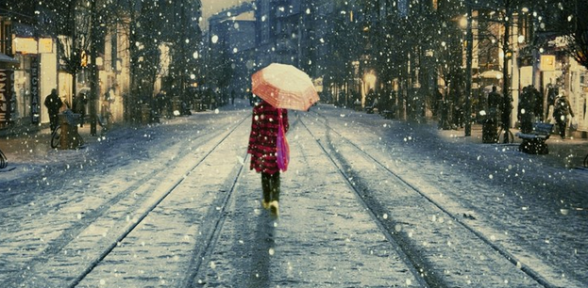 A woman in a red coat with a peach-colored umbrella walking down a snowy street in winter light.