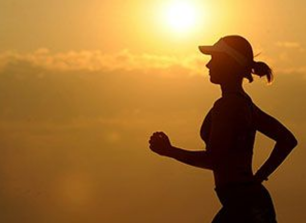 silhouette of a lean female runner against a sunny amber background