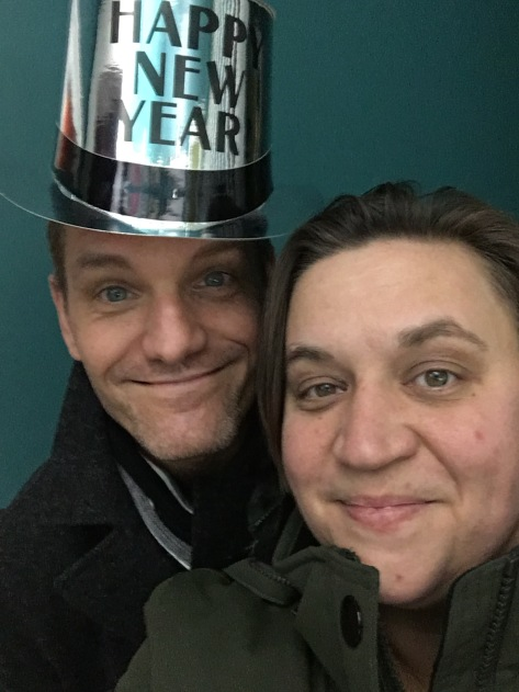 Natalie and her partner, wearing a silver cardboard hat with Happy New Year written on it, smile at the camera