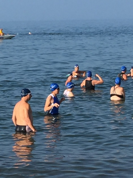 A group of swimmers in blue caps, standing in waist deep, calm lake water waiting for the start of a triathlon. Front end of safety kayak visible in the distance.