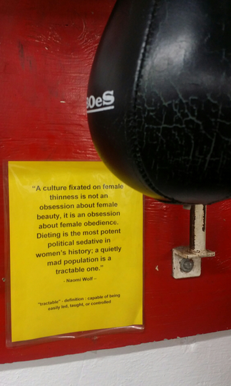 A punching bag against a red wall and yellow sign