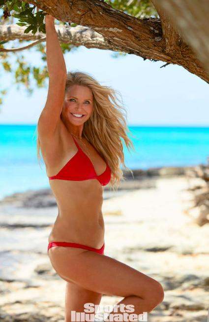 Photo description: This coloured photo depicts supermodel Christie Brinkley, age 63, blond and smiling, on a beach in a red bikini, with her right arm above her head holding a tree limb and her right leg bent at the knee. Turquoise water is in the background. It says Sports Illustrated. Photo credit: Emmanuel Hauguel, Sports Illustrated.