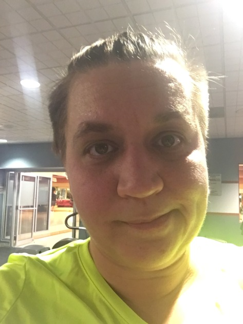A close up of Natalie's face making an unsure expression. She is sweaty with her hair pulled back. The backdrop is a gymnasium.