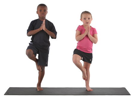 Two children doing tree balance pose on a yoga mat