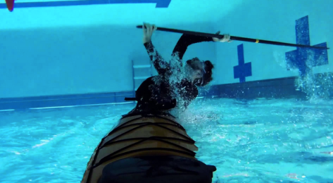 person in a sea kayak underwater in a pool, sweeping a paddle to come back up
