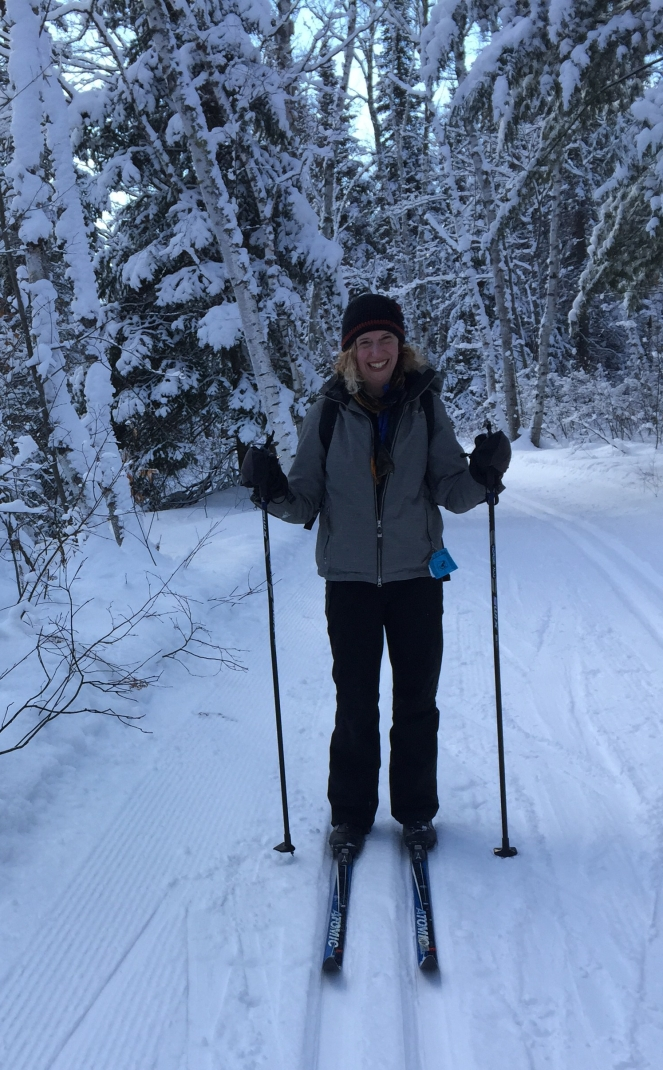 A white woman with a black hat, blond hair, grey jacket and black snow pants stands on a snow covered trail on cross country skis. Behind her is a grove of snow covered trees.