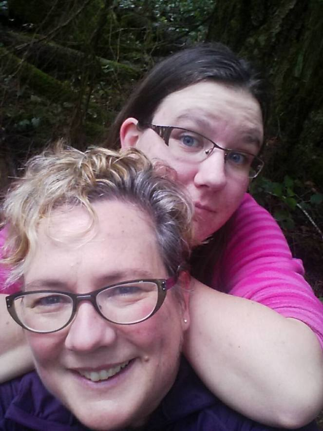 Image description:  A selfie featuring a mother being hugged from behind by her tall daughter in a leafy, mossy, green forest.